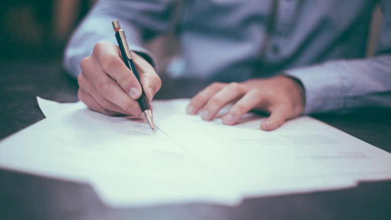 Close up of a man's hands holding a pen and signing a document